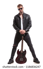 handsome rock star wearing sunglasses and leather jacket posing while holding his electric guitar and standing on white background