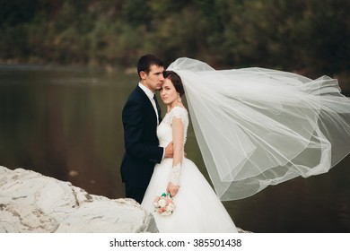 Handsome romantic groom and beautiful bride posing near river in scenic mountains
