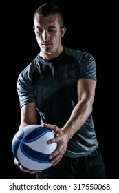 Handsome rugby player holding ball against black background