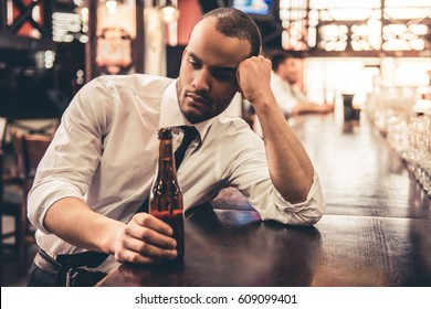 Handsome sad Afro American businessman is drinking beer and leaning on the bar counter while sitting at the pub