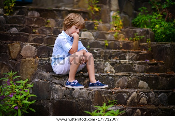 A handsome sad little boy sitting on the stone step of the old stairs and thinking about something