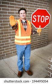 Handsome school crossing guard holding a stop sign.