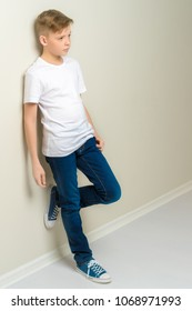 A handsome school-age boy leaned against the wall. The concept of youth fashion and culture.