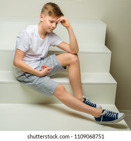 A handsome school-age boy sits on a white staircase. The concept of youth culture.