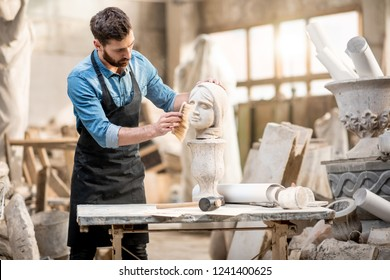 Handsome sculptor brushing sculpture of the woman's head at the working place in the old atmospheric studio