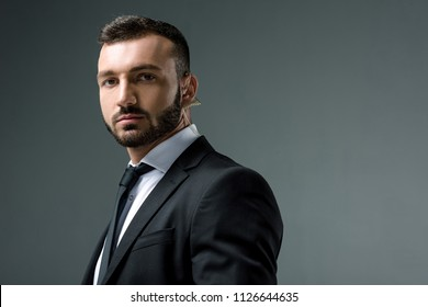 handsome security guard with security earpiece looking at camera isolated on grey