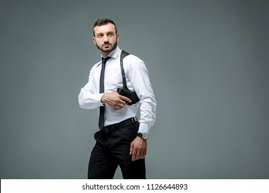 handsome security guard taking gun and looking away isolated on grey