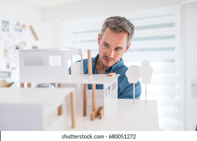 Handsome senior architect working on a construction project, he examines the model on which he works