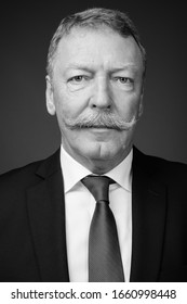 Handsome senior businessman with mustache against gray background