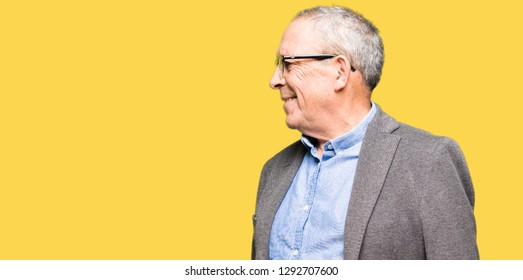 Handsome senior businesss man wearing glasses looking away to side with smile on face, natural expression. Laughing confident.
