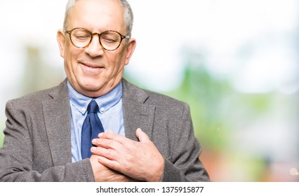 Handsome senior businesss man wearing glasses and tie smiling with hands on chest with closed eyes and grateful gesture on face. Health concept.