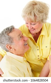 A handsome senior couple looking adoringly into each others eyes.  On a white background.