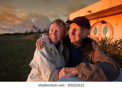Handsome senior couple looking toward a sunset outside