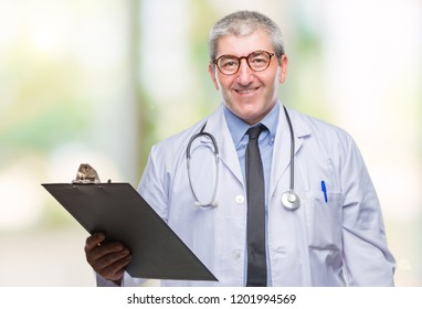 Handsome senior doctor man holding clipboard over isolated background with a happy face standing and smiling with a confident smile showing teeth