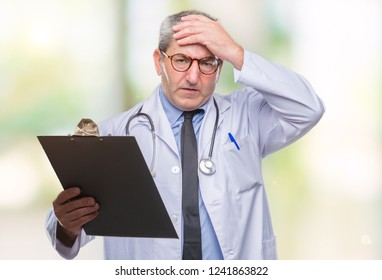 Handsome senior doctor man holding clipboard over isolated background stressed with hand on head, shocked with shame and surprise face, angry and frustrated. Fear and upset for mistake.