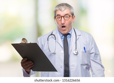 Handsome senior doctor man holding clipboard over isolated background scared in shock with a surprise face, afraid and excited with fear expression