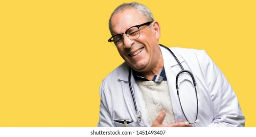 Handsome senior doctor man wearing medical coat Smiling and laughing hard out loud because funny crazy joke. Happy expression.