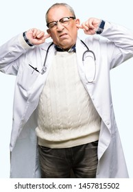 Handsome senior doctor man wearing medical coat covering ears with fingers with annoyed expression for the noise of loud music. Deaf concept.