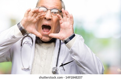 Handsome senior doctor man wearing medical coat Shouting angry out loud with hands over mouth