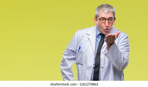 Handsome senior doctor, scientist professional man wearing white coat over isolated background looking at the camera blowing a kiss with hand on air being lovely and sexy. Love expression.