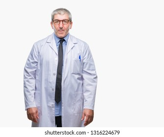 Handsome senior doctor, scientist professional man wearing white coat over isolated background with serious expression on face. Simple and natural looking at the camera.