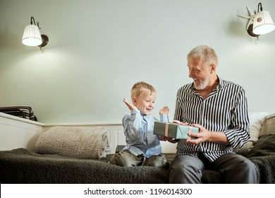 Handsome senior grandfather presenting gift to happy grandson while sitting on sofa in living room