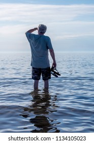 A handsome senior male walks in the warm waters of Lake Michigan, with his sandles in his hand