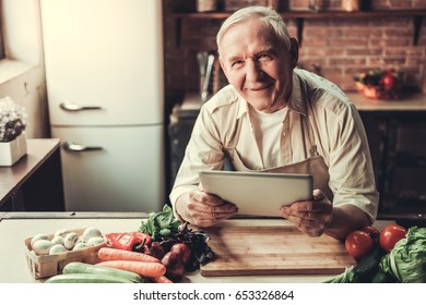 Handsome senior man in apron is using a digital tablet, looking at camera and smiling while cooking in kitchen