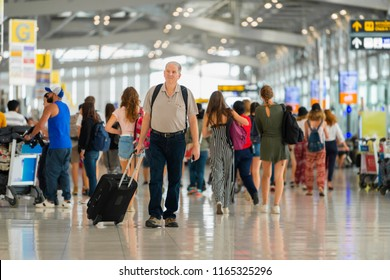 Handsome senior man with backpack walking with a luggage at airport terminal and airport terminal blurred crowd of travelling people on the background.