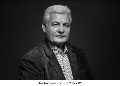 Handsome senior man in blazer on dark background, black and white effect