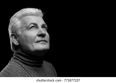 Handsome senior man in casual clothes on dark background, black and white effect