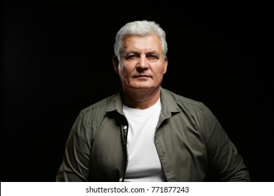 Handsome senior man in casual clothes on black background