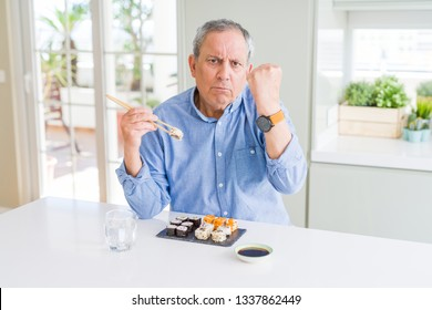 Handsome senior man eating take away sushi using chopsticks at home annoyed and frustrated shouting with anger, crazy and yelling with raised hand, anger concept