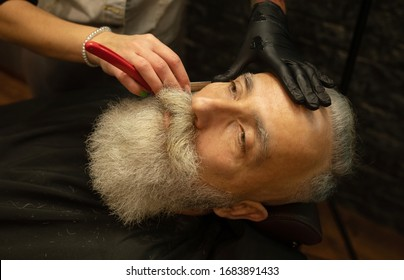 Handsome senior man getting styling and trimming of his beard in the barbershop.