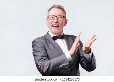 Handsome senior man in glasses and suit applauding