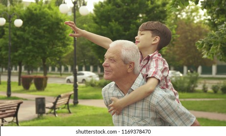 Handsome senior man holding his grandson on his back outdoors. Attractive little boy riding his grandpa on walkway in the park. Brunette caucasian kid pointing his hand forward