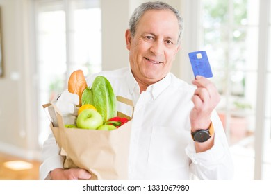 Handsome senior man holding paper bag full of fresh groceries and showing credit card as payment