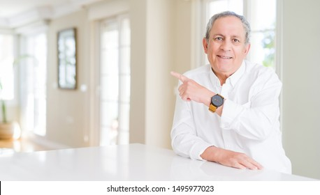 Handsome senior man at home cheerful with a smile of face pointing with hand and finger up to the side with happy and natural expression on face