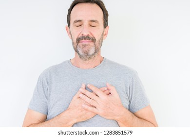 Handsome senior man over isolated background smiling with hands on chest with closed eyes and grateful gesture on face. Health concept.