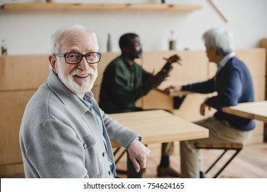 handsome senior man sitting in cafe and looking at camera