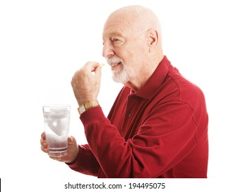 Handsome senior man stays healthy by taking a fish oil supplement with a glass of water.   Isolated on white.