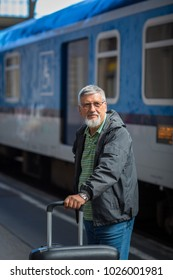 Handsome senior man taking a train, waiting for his family to pick him up (color toned image)