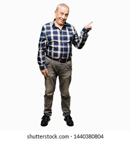 Handsome senior man wearing casual shirt with a big smile on face, pointing with hand and finger to the side looking at the camera.