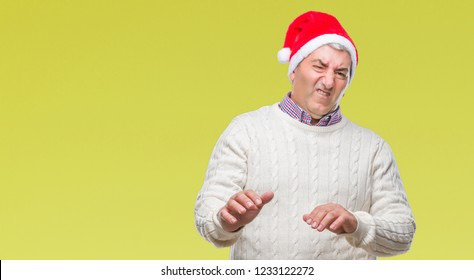 Handsome senior man wearing christmas hat over isolated background disgusted expression, displeased and fearful doing disgust face because aversion reaction. With hands raised. Annoying concept.