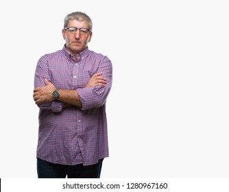 Handsome senior man wearing glasses over isolated background skeptic and nervous, disapproving expression on face with crossed arms. Negative person.