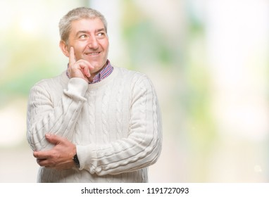 Handsome senior man wearing winter sweater over isolated background with hand on chin thinking about question, pensive expression. Smiling with thoughtful face. Doubt concept.