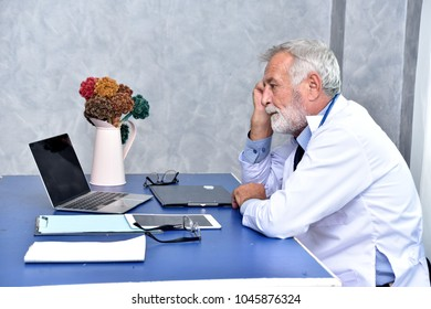 Handsome senior medical doctor in white coat is thinking and looking seriously at  doctor's office