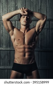Handsome sensual serious young boy brunet with muscular bare torso strong abdominal and biceps muscles looking straight in black male trendy underpants posing on gray wooden background, vertical