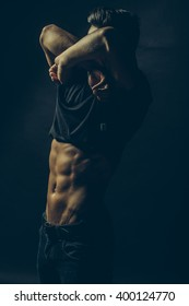 Handsome sensual sexy young stylish thoughtful man in black shirt with fashionable hairdo undressing with bare muscular torso and beautiful body indoor on studio background, vertical picture