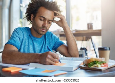 Handsome serious black European male student busy learning lessons during lunch at cafe, sitting at table with food and textbooks, making notes, writing down new words preparing for Spanish class
